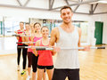 Group of smiling people working out with barbells fitness sport training gym and lifestyle concept in the gym Royalty Free Stock Photos