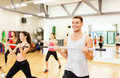 Group of smiling people working out with barbells fitness sport training gym and lifestyle concept in the gym Royalty Free Stock Photo