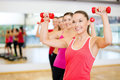 Group of smiling people working out with dumbbells fitness sport training gym and lifestyle concept in the gym Stock Photography