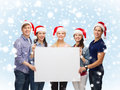Group of smiling students with white blank board education advertisement sale christmas and people concept in santa helper hats Stock Image
