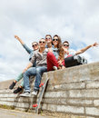 Group of smiling teenagers hanging out summer holidays and teenage concept with boob box and skatboard outside Royalty Free Stock Photo