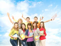 Group of smiling teenagers jumping together and looking at camera over a blue sky background Stock Photography