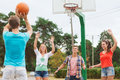 Group of smiling teenagers playing basketball summer vacation holidays games and friendship concept outdoors Stock Photography
