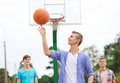 Group of smiling teenagers playing basketball summer vacation holidays games and friendship concept outdoors Royalty Free Stock Photo