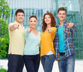 Group of smiling teenagers pointing fingers on you friendship business education and people concept over campus background Stock Photo