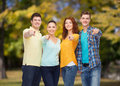 Group of smiling teenagers pointing fingers on you friendship summer vacation nature and people concept finger over green park Royalty Free Stock Image