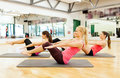 Group of smiling women exercising on mats in gym Royalty Free Stock Images
