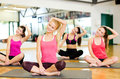 Group of smiling women stretching on mats in gym fitness sport training and lifestyle concept the Stock Images