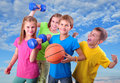 Group of sporty children friends with dumbbells and ball against blue sky childhood happiness active sports lifestyle concept Royalty Free Stock Image