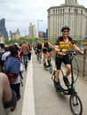 stock image of  Group of standing elliptical bicyclists riding on a crowded Brooklyn Bridge. May 2018.