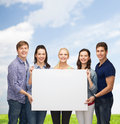 Group of standing students with blank white board education and people concept smiling Stock Image