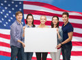 Group of standing students with blank white board education and people concept smiling Stock Photos
