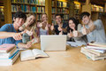 Group of students giving thumbs up sitting in a library at a table while using the laptop and Stock Photos