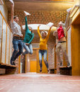 Group of students jumping in college corridor full length a Stock Photo