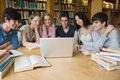 Group of students learning in a library sitting at table while and using the laptop Royalty Free Stock Photo