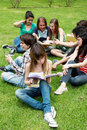 Group of students sitting in park Royalty Free Stock Photo