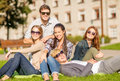 Group of students or teenagers hanging out summer holidays education campus and teenage concept outdoors Royalty Free Stock Image
