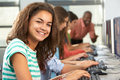 Group of students working at computers in classroom smiling to camera Royalty Free Stock Photo