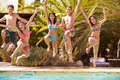 Group Of Teenage Friends Jumping Into Swimming Pool Royalty Free Stock Photo