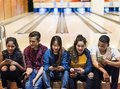 Group of teenage friends using smartphone in a bowling alley Royalty Free Stock Photo
