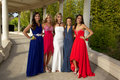 A group of teenage girls posing in their prom dresses beautiful at the smiling and Stock Photos