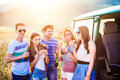 Group of teenage hipsters on roadtrip drinking beer eating a young friends outside a summer day Royalty Free Stock Images