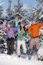 Group of teenagers jumping together in wintertime snowy forest Royalty Free Stock Photos
