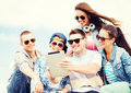 Group of teenagers looking at tablet pc summer holidays teenage and technology concept taking picture with Royalty Free Stock Photo