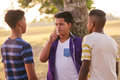 Group of Teenagers In Park Boy Smoking Electronic Cigarette Royalty Free Stock Photo