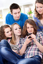 Group of teenagers reading interesting sms Royalty Free Stock Photography