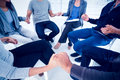 Group therapy in session sitting in a circle bright room Royalty Free Stock Photos
