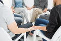 Group therapy in session sitting in a circle with therapist Royalty Free Stock Images