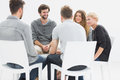 Group therapy in session sitting in a circle with therapist Royalty Free Stock Photography