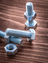 Group of threaded stainless bolts and screw nuts on vintage wooden board construction concept Royalty Free Stock Photos