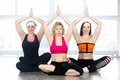 Group of three yogi females sitting in easy pose sporty girls doing fitness exercises class yoga sukhasana decent pleasant with Royalty Free Stock Photo