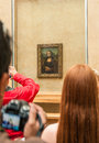 Group of tourists gathered around the Mona Lisa in the Louvre Museum. Royalty Free Stock Photo