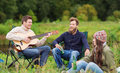 Group of tourists playing guitar in camping Royalty Free Stock Photo