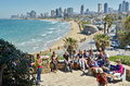 A group of turists near the mediterranean tel aviv israel apr beach and tel aviv israel boradwalk with city sky line and Royalty Free Stock Image