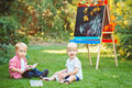Group of two white Caucasian toddler children kids boy and girl sitting outside in summer autumn park by drawing easel Royalty Free Stock Photo