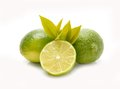 Group of whole and cut fresh limes with leaves on white Royalty Free Stock Photos