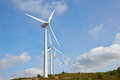 Group of windmills for renewable electric energy production on blue sky Royalty Free Stock Photo