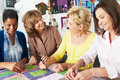 Group of women making quilt together and talking Stock Photos