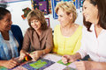 Group of women making quilt together and talking Stock Photo