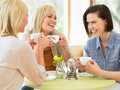 Group of women meeting in cafe smiling to each other Royalty Free Stock Photography