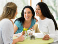 Group of women meeting in cafe smiling to each other Stock Photography