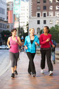 Group of women power walking on urban street smiling Royalty Free Stock Photos