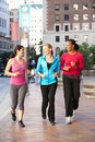 Group of women power walking on urban street smiling Stock Photo