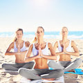 Group of women practising yoga on the beach Royalty Free Stock Photo