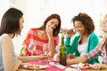 Group of women sitting around table eating dessert and having a chat laughing Stock Photos