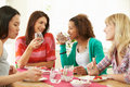 Group of women sitting around table eating dessert talking to each other holding glass water Royalty Free Stock Photo
